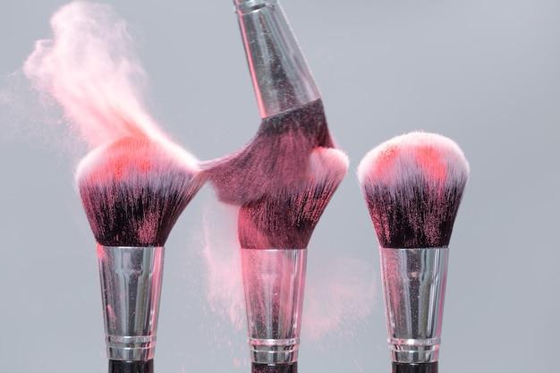 핑크 파우더 스플래시와 밝은 배경에 파우더 브러쉬를 닫습니다.