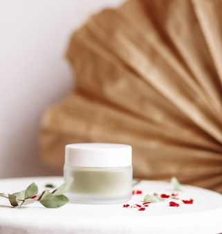パウダーコスメティックマスク。乾燥した花びらと白い背景に抹茶とガラスの瓶。