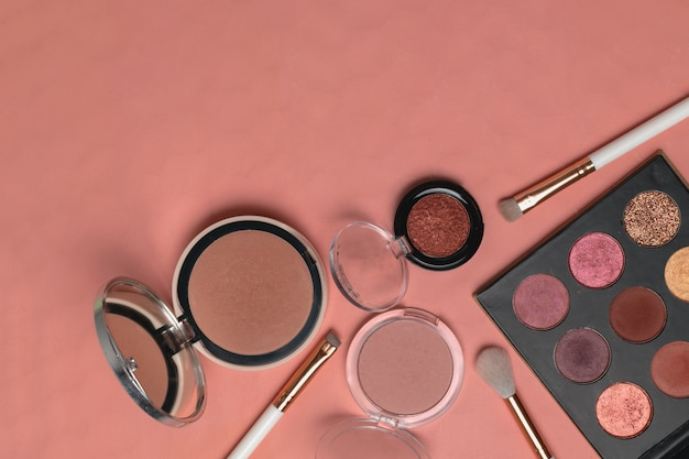 Powder, eyeshadows, makeup brushes on trendy living coral