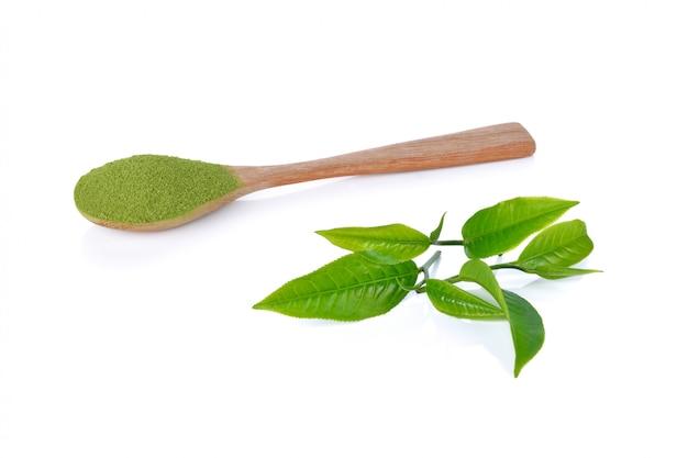 Порошок зеленого чая и листьев зеленого чая на белом