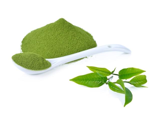 Порошок зеленого чая и листьев зеленого чая, изолированные на белом