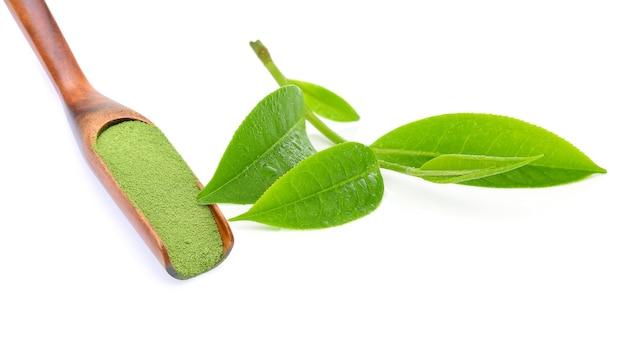 Порошок зеленого чая с листьями зеленого чая, изолированными на белом.
