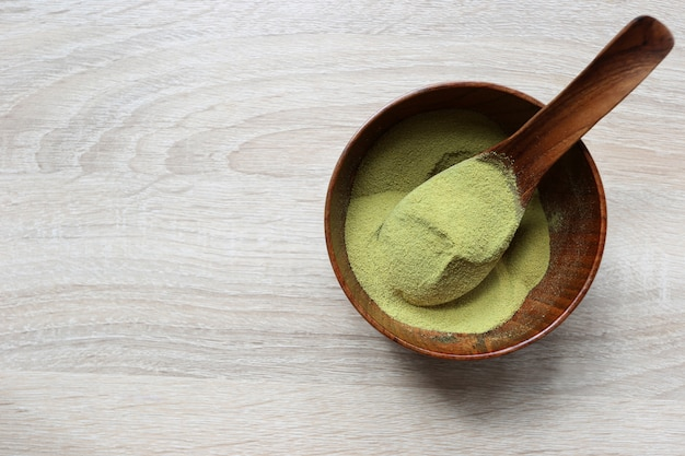 Powder matcha green tea in a bowl on wood