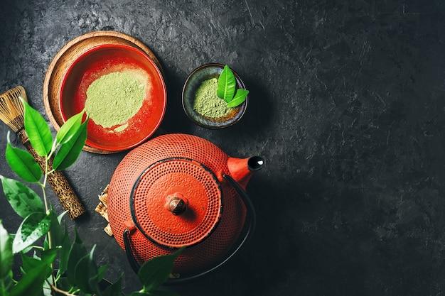 Порошок чая матча с чайником на темном фоне