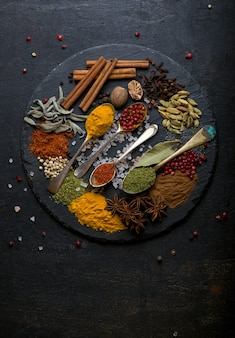 Powder spices on spoons in black wooden table background.