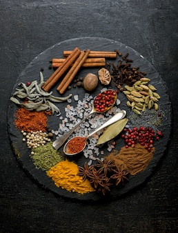 Powder spices on spoons in black wooden table.