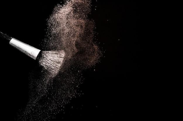 Powder splash and brush for makeup artist in black background