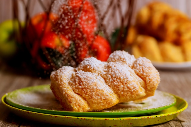 Powdered apple strudel on green plate with fresh apples