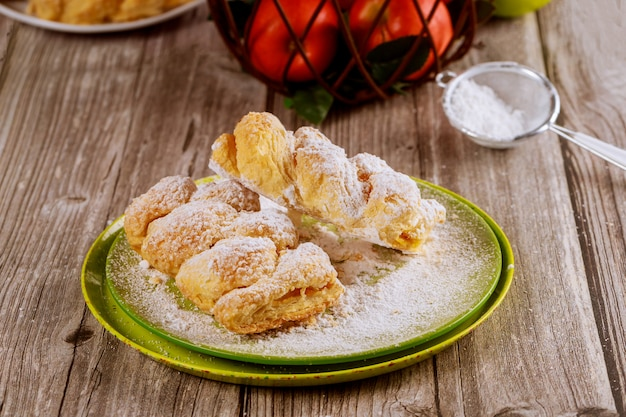 Powdered apple strudel on green plate with fresh apples.