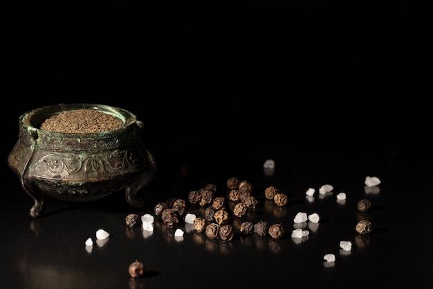 黒い表面に粉末の黒コショウとコショウのトウモロコシ Premium写真