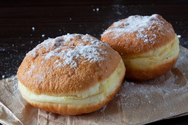 Powdered doughnuts on the dark background