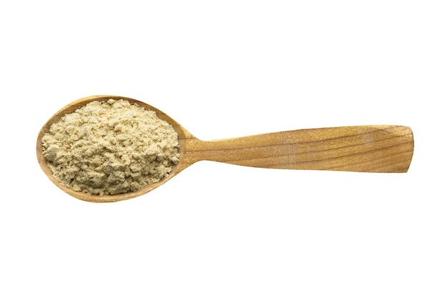 Powdered ginger for adding to food. spice in wooden spoon isolated on white. seasoning of delicious meal.