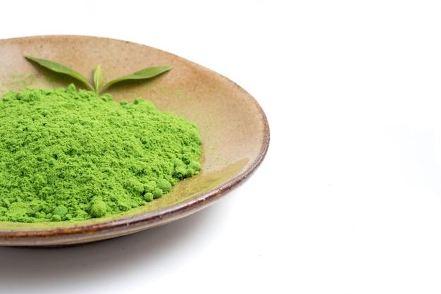 Порошок зеленый чай в керамической плиты на белом фоне.