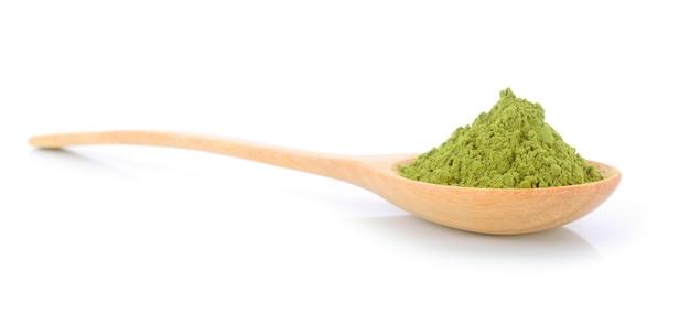 白い背景で隔離のスプーンで粉末抹茶緑茶
