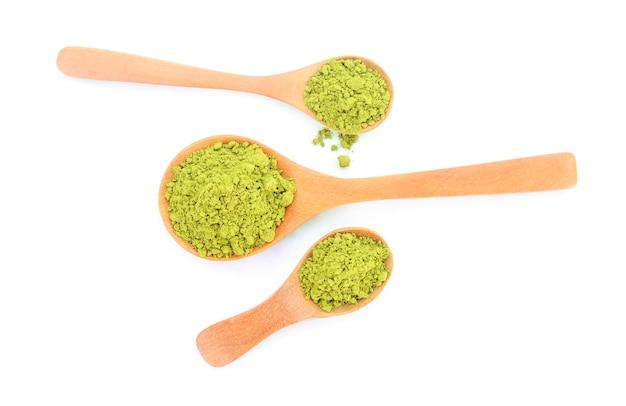 Порошок зеленого чая матча в деревянной ложке, изолированные