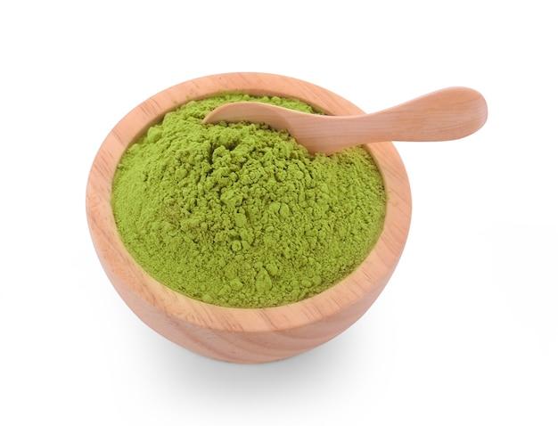 白い表面に分離された木のスプーンで粉末抹茶緑茶