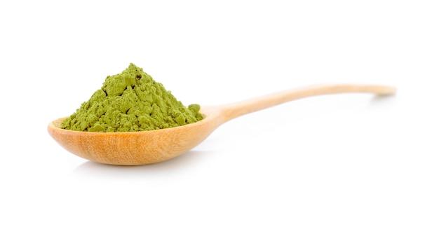 Порошок зеленого чая матча с ложкой на белом