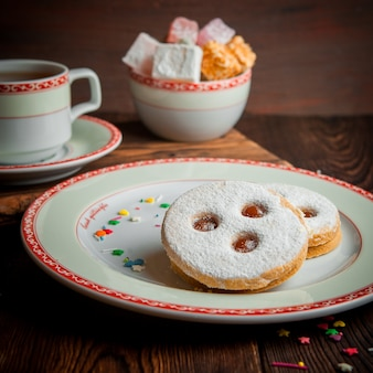 Biscotti di zucchero a velo con una tazza di tè e zucchero nel piatto rotondo