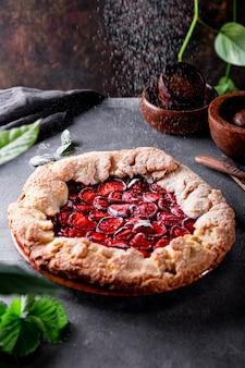 가루 설탕을 테이블에 딸기와 함께 홈메이드 파이에 붓고 여름 패스트리와 함께