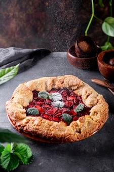가루 설탕을 테이블에 딸기와 함께 홈메이드 파이에 붓고 여름 패스트리와 함께 프리미엄 사진