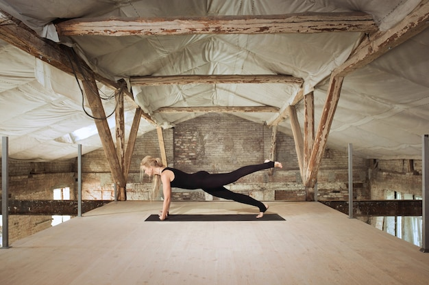 힘. 젊은 체육 여자 버려진 된 건설 건물에 요가 연습. 정신적 및 신체적 건강 균형. 건강한 라이프 스타일, 스포츠, 활동, 체중 감소, 집중력의 개념.