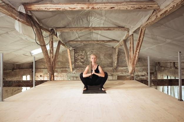 力。若いアスリートの女性は、放棄された建設ビルでヨガを練習します。心身の健康バランス。健康的なライフスタイル、スポーツ、活動、減量、集中の概念。