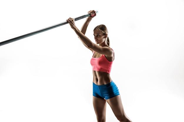 힘과 아름다움과 순수함. 흰 벽에 전문 여성 장대 높이뛰기 훈련. 핏과 날씬한 여성 모델 연습. 스포츠의 개념,