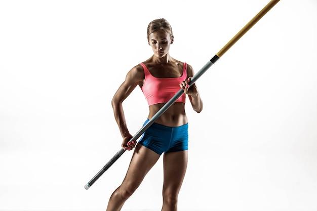 力強さと美しさと純粋さ。白い壁でトレーニングするプロの女性棒高跳び選手。フィットしてスリムな女性モデルの練習中。スポーツのコンセプト、