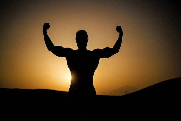 Сила и свобода, мускулистый силуэт мужчины на фоне огненного заката неба в горах, спорт и отдых, будущее и успех, люди и природа, скорость и здоровый образ жизни, йога и фитнес