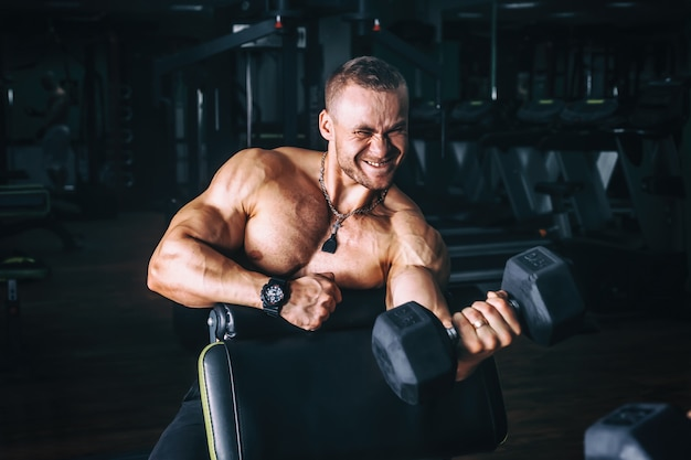 Power athletic guy bodybuilder, execute exercise with dumbbells,