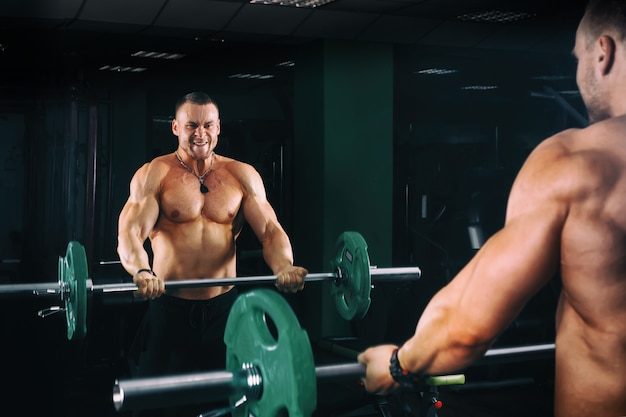Power athletic guy bodybuilder working out biceps with barbell in front of mirrors