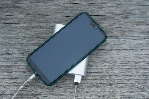 Power Bank는 공원의 나무 벤치에서 스마트폰을 충전합니다. 프리미엄 사진