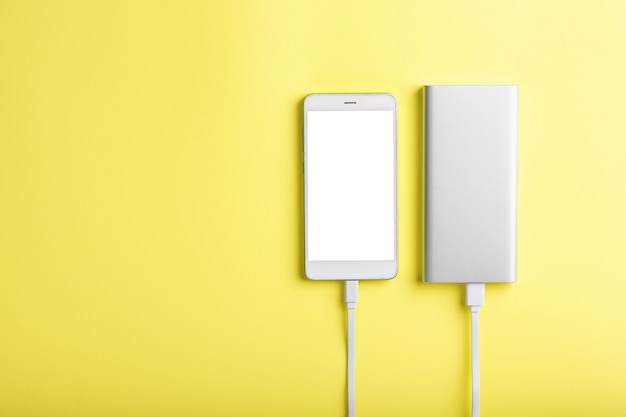 Power bank는 노란색 표면에 스마트 폰을 충전합니다.