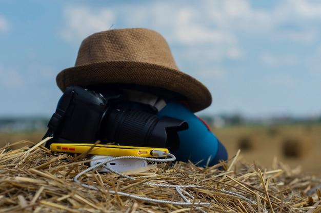 파워뱅크는 자연 속 건초를 배경으로 가방과 모자를 든 카메라를 배경으로 스마트폰을 충전한다. 휴대용 여행용 충전기.