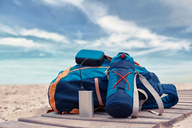 Power bank charges a musical speaker against a backdrop of journey bags at the beach on a cloudy day