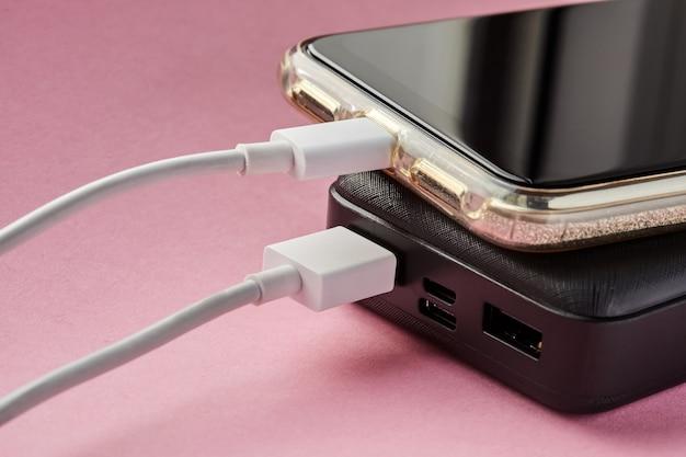 Power bank заряжает смартфон с помощью usb-кабеля на розовой поверхности
