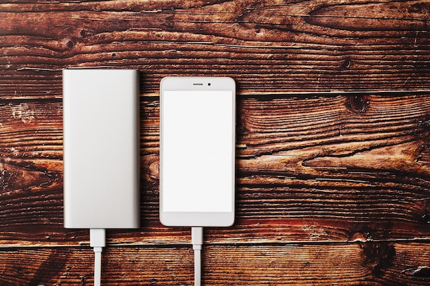 Power bank charges a smartphone on a wooden background.