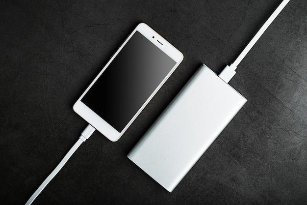 Power bank는 어두운 표면에서 스마트 폰을 충전합니다.