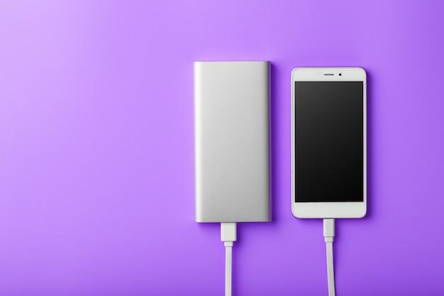Power bank는 자주색 배경에 스마트 폰을 충전합니다. 가제트 여유 공간과 최소한의 구성을위한 범용 외부 배터리.