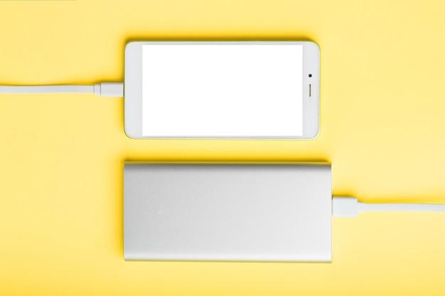 Power bank는 노란색 표면에서 스마트 폰을 충전합니다.
