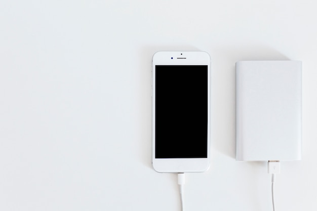 Power bank charging smart phone over the white backdrop
