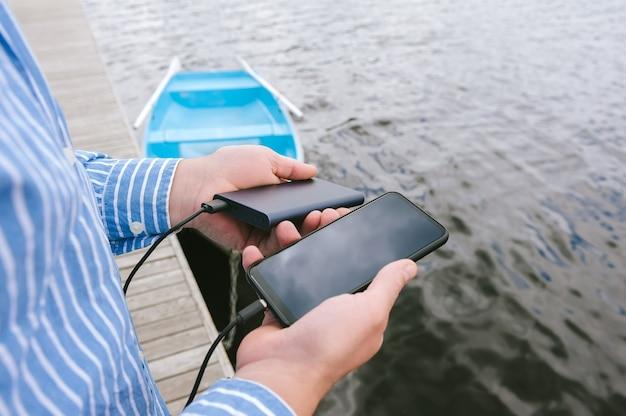 남자의 손에 스마트폰을 충전하는 파워 뱅크. 물과 부두에 보트를 배경으로.