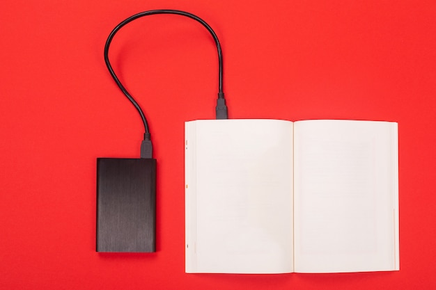 Power bank connected by cable to the opened notepad isolated  red
