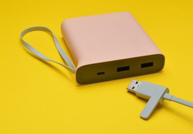 黄色の背景にusbケーブルのクローズアップでスマートフォンとガジェットを充電するための電源銀行。現代のテクノロジー。