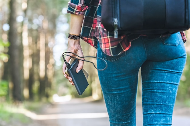 Power bank in the girl s hand, against the forest and the road.