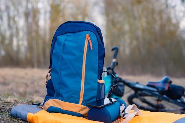 Пауэрбанк с кабелем на фоне сумки и велосипеда в лесу