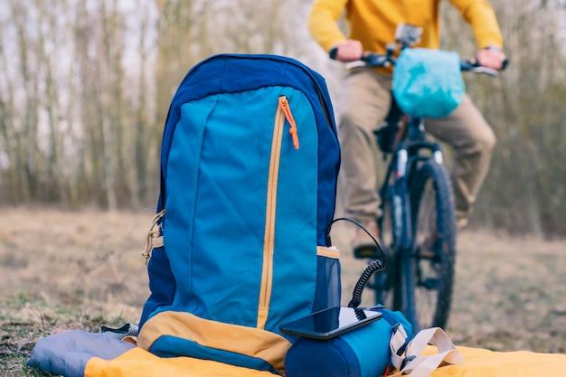 Павербанк с кабелем на фоне сумки и велосипедиста в лесу
