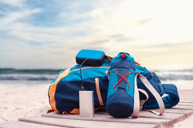 Power bank заряжает музыкальный динамик на фоне дорожных сумок на пляже в пасмурный день