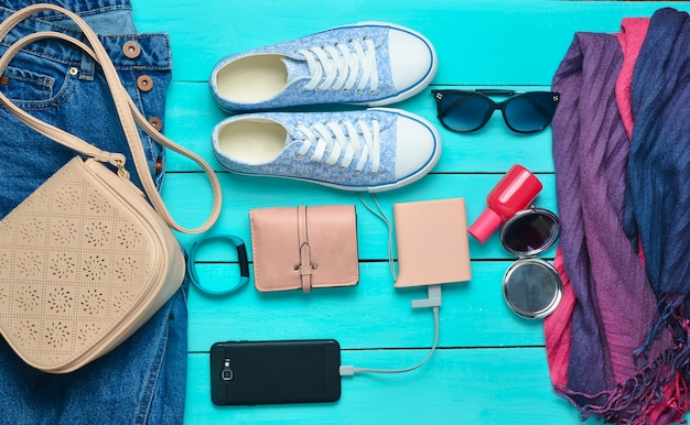 Модные женские аксессуары, обувь, одежда и современные гаджеты на синем фоне деревянных. джинсы, сумка, кроссовки, смартфон, умный браслет, power bank, косметика, солнцезащитные очки, шарф. вид сверху.