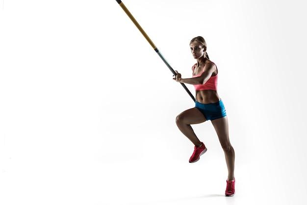 Potenza, bellezza e purezza. formazione professionale femminile del saltatore con l'asta sulla parete bianca. pratica modello femminile in forma e sottile. concetto di sport,